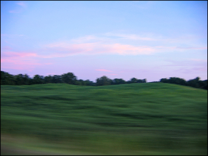 A landscape scene photographed from a moving car. It is a field in rural Allen County, Indiana.