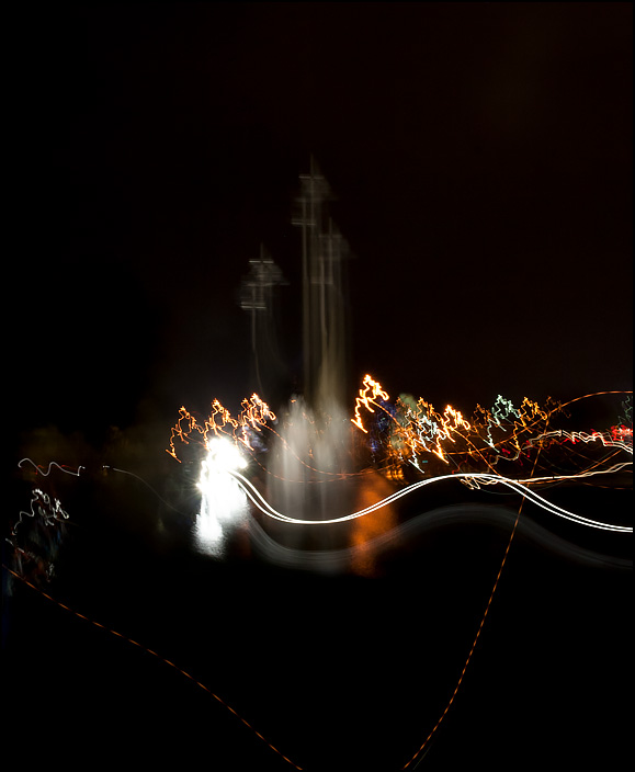 Blurred lines of moving colorful lights around a fountain and crosses outside a church at night.