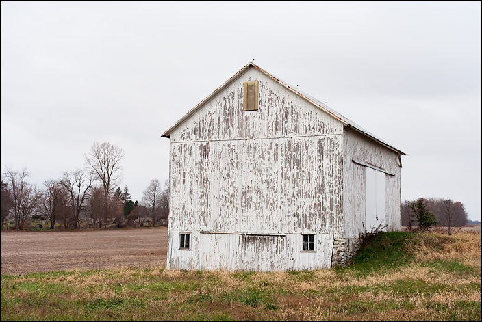 A white barn with peeling paint stands on a hill in a field on State Road 205 in rural Whitley County, Indiana.