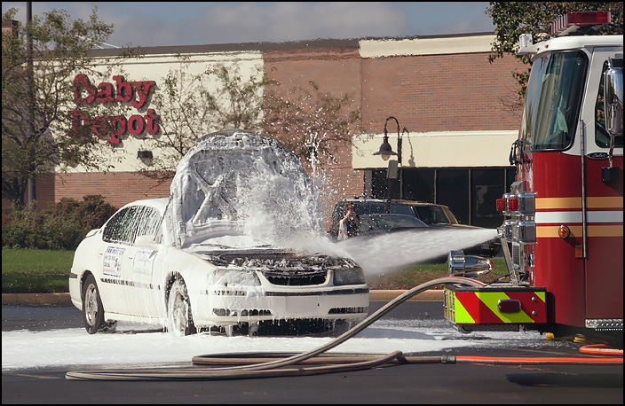 Firefighters shoot fire retarding foam at a car that caught fire in the parking lot of a shopping center in Fort Wayne, Indiana. The entire engine compartment and front of the car are coated in thick white foam.