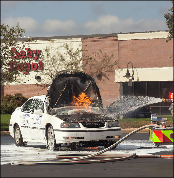 The fire in the engine compartment of a burning car resumed after firefighters stopped spraying it with foam, so they began spraying it again.