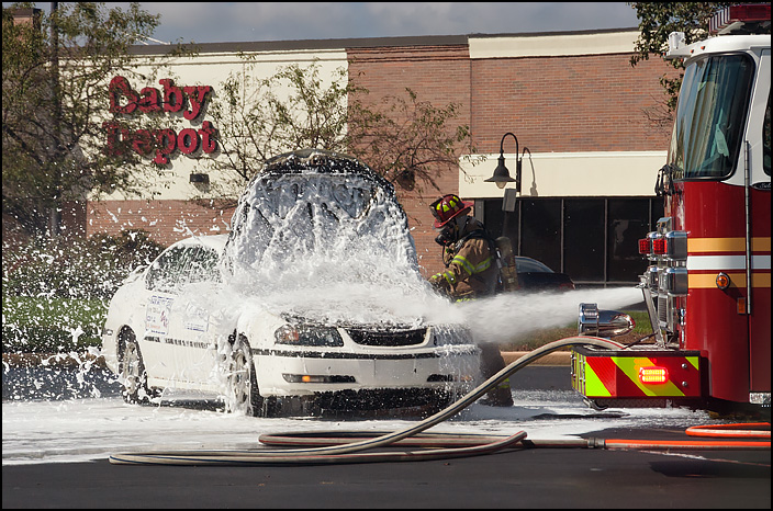 Firemen drench the engine compartment of a burning car with fire retardant foam.