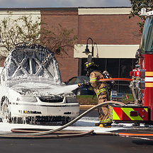Photographs of firefighters putting out a fire under the hood of a car by Ariana Thompson.